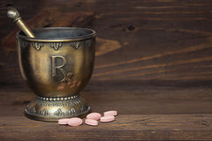 RX mortar and pestle with pink tablets on wood background. Rx mortar and pestle with pink tablet on wood  background representing old, vintage pharmaceutical and Royalty Free Stock Photography