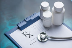 Rx prescription on clipboard with stethoscope. And pills Royalty Free Stock Photography