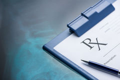 RX prescription form and pen on stainless. Steel desk blue tone Stock Photos
