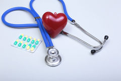 RX prescription, Red heart, asorted pils and a stethoscope on white background.  Royalty Free Stock Photos