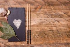 Ryżowy serce kształtował z czosnkiem i podpalanym liściem, odgórny widok Obrazy Stock