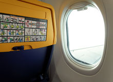 Ryanair aircraft seat with safety info by window. New seat inside a Ryanair Boeing 737 800 aircraft with safety info card Stock Images