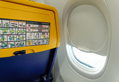 Ryanair aircraft seat with safety info by window. New seat inside a Ryanair Boeing 737 800 aircraft with safety info card Royalty Free Stock Image