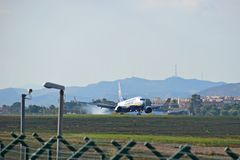 Ryanair Airplane Landing. The aircraft smokes the tyres as it touches down at Alicante airport Royalty Free Stock Photography