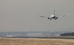 Ryanair jet airliner approach to land at Madrid airport runway, seen from behind Royalty Free Stock Photography