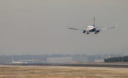 Ryanair scaturisce approccio dell'aereo di linea a terra alla pista dell'aeroporto di Madrid, veduta da dietro Fotografia Stock Libera da Diritti