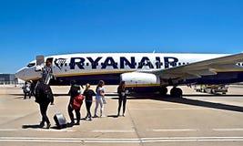 Ryanair-vliegtuig bij een luchthaven met mensen stock foto's
