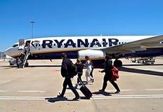 Ryanair-vliegtuig bij een luchthaven met mensen stock foto