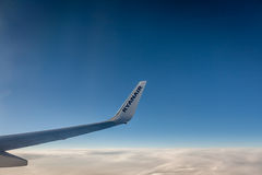 Ryanair wing. Ryanair plane winglet above the clouds at sunset Royalty Free Stock Images