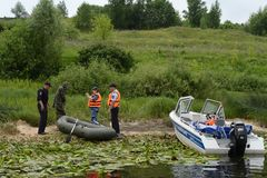 Police officers draw up a protocol for the man for poaching on the Oka River. RYAZAN, RUSSIA - JUNE 16, 2015: Police officers draw up a protocol for the man for Stock Photos