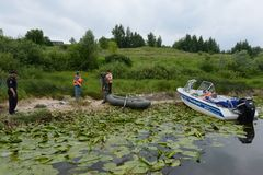 Police officers draw up a protocol for poaching on the river. RYAZAN, RUSSIA - JUNE 16, 2015: Police officers draw up a protocol for poaching on the river Royalty Free Stock Images