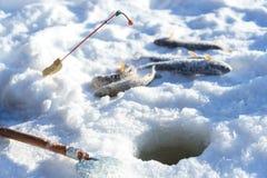 Ryba i prącie na lodzie blisko do dziury podczas gdy zima połów Obrazy Royalty Free