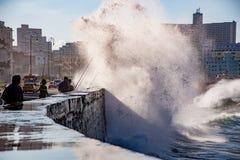 Rybacy stoją ich ziemię jak fala rozbijają nad Malecon wal Fotografia Stock