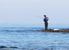 Rybak łapie ryba na przędzalnictwie przy zima rankiem Zdjęcie Stock