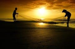 Rybak i rybaczka pracuje podczas wschodu słońca Zdjęcia Royalty Free