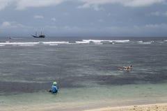 Rybak i surfingowowie przy Serangan pla?? zdjęcie stock
