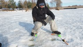 Rybak musztruje dziury w lodu zakończeniu w górę widoku, sporta połów w zimie zbiory