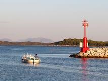 Rybak na łodzi pływa out łapać ryba w promieniach wczesny słońce Mężczyzna na łodzi żegluje past kamienny falochron z a zdjęcia royalty free