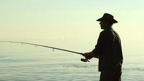 Rybak na jeziorze w kowbojskim kapeluszu zbiory wideo