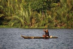 Rybak patrzeje dla ryba w rzece z łodzią Zdjęcie Royalty Free