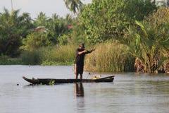 Rybak patrzeje dla ryba w rzece z łodzią Obraz Stock