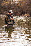 Rybak pozycja w rzece gdy łowiący dla pstrąg Zdjęcia Stock