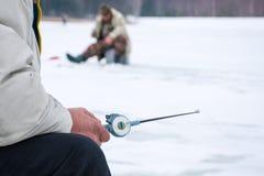 Rybak siedzi z zima połowu prąciem w ręce w przedpolu w tło zamazywać sylwetkach rybacy na ic, fotografia stock