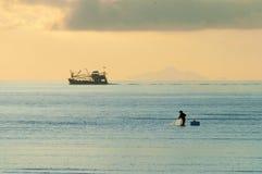 Rybak sylwetka z łodzią rybacką behind Obraz Stock