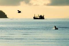 Rybak sylwetka z łodzią rybacką behind Zdjęcia Royalty Free