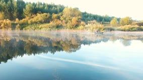 Rybak unosi się na rzece w jesieni na nadmuchiwanej motorowej łodzi zbiory