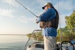 Rybak w łodzi rybackiej na rzece łowi zdjęcie royalty free