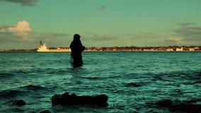 Rybak w wodzie przy zmierzchem, Laboe linia brzegowa, Kiel zbiory