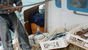 Rybak wyciąga rybiego chwyta od sieci rybackich i rzutu w kosz Starszy żeglarz w porcie Bodrum, Turcja zdjęcie wideo