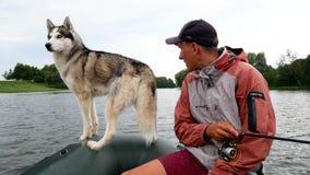Rybak z łuskowatym psem w łodzi zbiory wideo