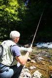 Rybak z połowu haczykiem w rzece zdjęcie royalty free