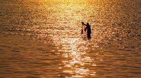 Rybak z siecią w morzu z zmierzchu światła odbiciem na dennym wa Fotografia Royalty Free