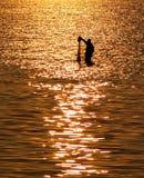 Rybak z siecią w morzu z zmierzchu światła odbiciem na dennym wa Obrazy Royalty Free