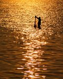 Rybak z siecią w morzu z zmierzchu światła odbiciem na dennym wa Fotografia Stock