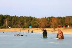 Rybaka chwyta ryba w zamarzniętym łupie n zima przeciw tłu lasowi zima krajobrazu rybacy na lodzie przeciw obraz royalty free