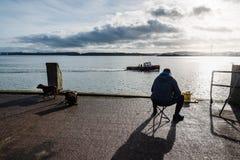 Rybaka obsiadanie na doku zatoka fotografia royalty free