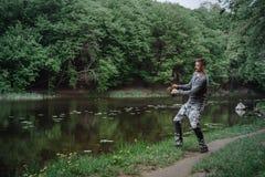Rybaka połowu lany prącie w jeziorze lub wodzie rzecznej Mężczyzna z przędzalnictwo sprzętem w zielonym lasowym Zdrowym stylu życ Zdjęcia Royalty Free