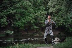 Rybaka połowu lany prącie w jeziorze lub wodzie rzecznej Mężczyzna z przędzalnictwo sprzętem w zielonym lasowym Zdrowym stylu życ Obraz Royalty Free