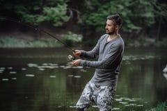 Rybaka połowu lany prącie w jeziorze lub wodzie rzecznej Mężczyzna z przędzalnictwo sprzętem w zielonym lasowym Zdrowym stylu życ Obrazy Stock