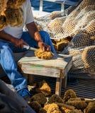 RYBAKA SIEDZĄCY rozcięcie DENNA gąbka Z nożem NA łodzi rybackiej zdjęcia stock