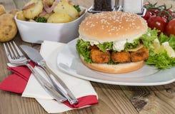 Rybi hamburger z smażyć grulami w pucharze Zdjęcia Royalty Free