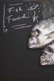 Rybi jedzenie, handwriting tekst na czarnym chalkboard tle z surowym dorado łowi, odgórny widok Obrazy Royalty Free