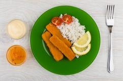 Rybi kije z ryż, majonez, ketchup, rozwidlenie na drewnianym stole fotografia stock