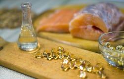 Rybi olej jest ciekły i w kapsułach od łososia Czerwonego łososia ryba świeża na drewnianej tnącej desce Olej omega 3 i omega 6 Obrazy Royalty Free