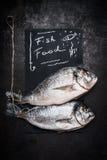 Rybiego jedzenia literowanie na czarnym chalkboard z dwa surowym całym dorado łowi na ciemnym rocznika tle, odgórny widok Owoce m obrazy stock