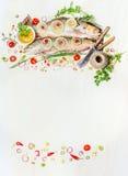 Rybiego jedzenia tło z surową całą ryba, świeżymi wyśmienicie kulinarnymi składnikami i cutlery na, białym drewnianym, odgórnym w zdjęcia stock